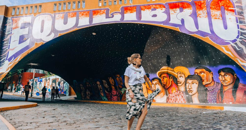 Young woman twirling on a cobbled street and under a colourfully painted bridge