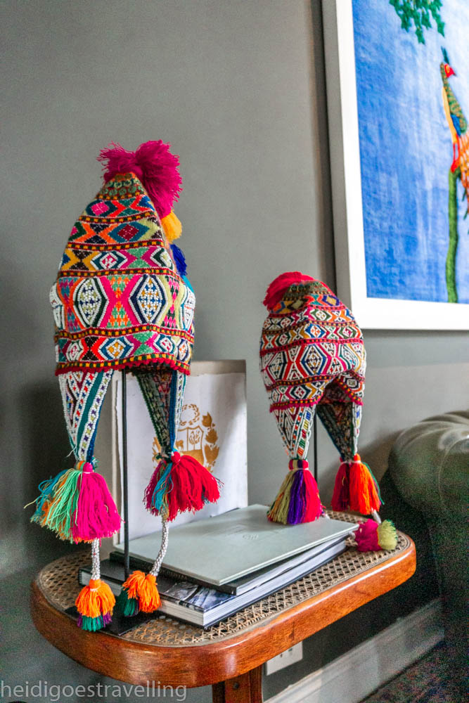 picture of two rainbow coloured traditional Peruvian hats on a couchside table
