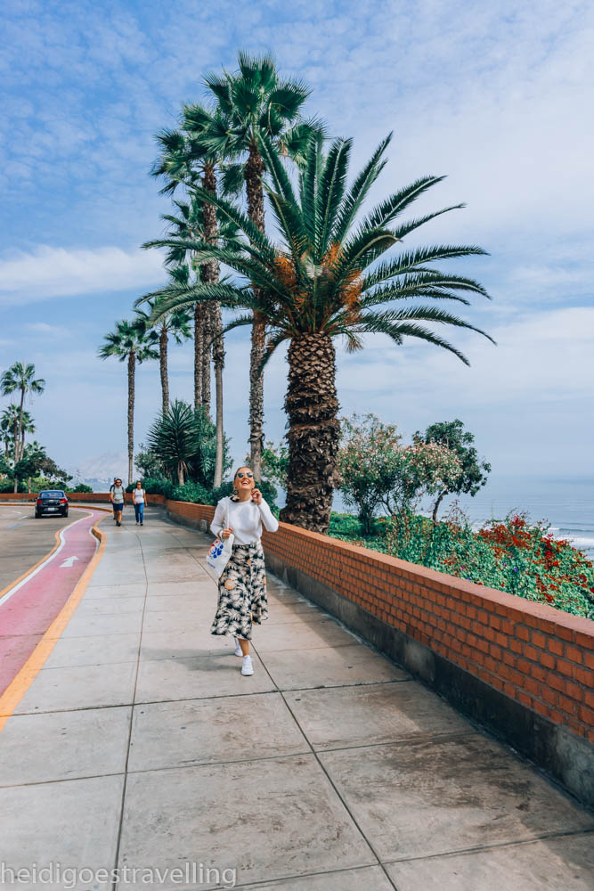 Young smiling woman walking down a palm tree lined street above the Pacific oceanstreet and under a colourfully painted bridge