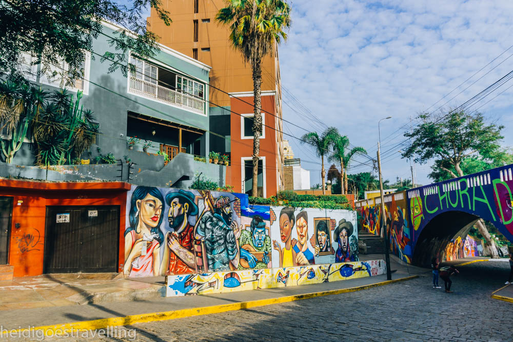 Wall covered by very colourful paintings representing people and towered over by three colourful art-deco buildings