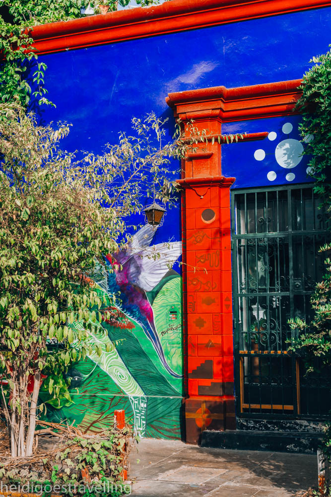 Close-up view of a door and wall all covered in red, blue and green art