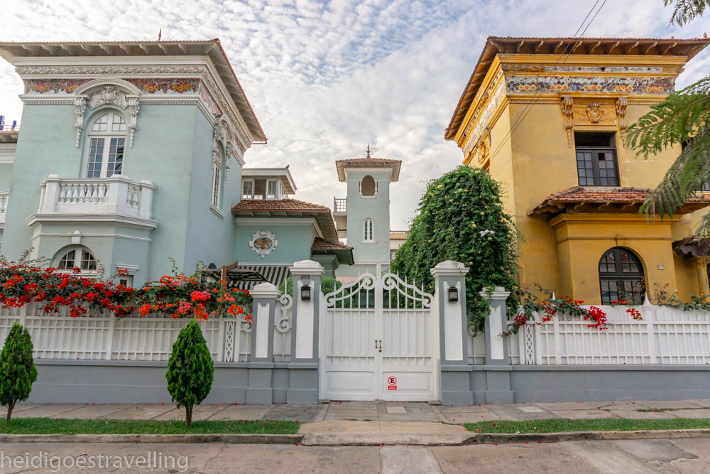 Front view of two 1920s buildings, one aqua and one mustard coloured gated by a high white fence and fuchsia and red flowers