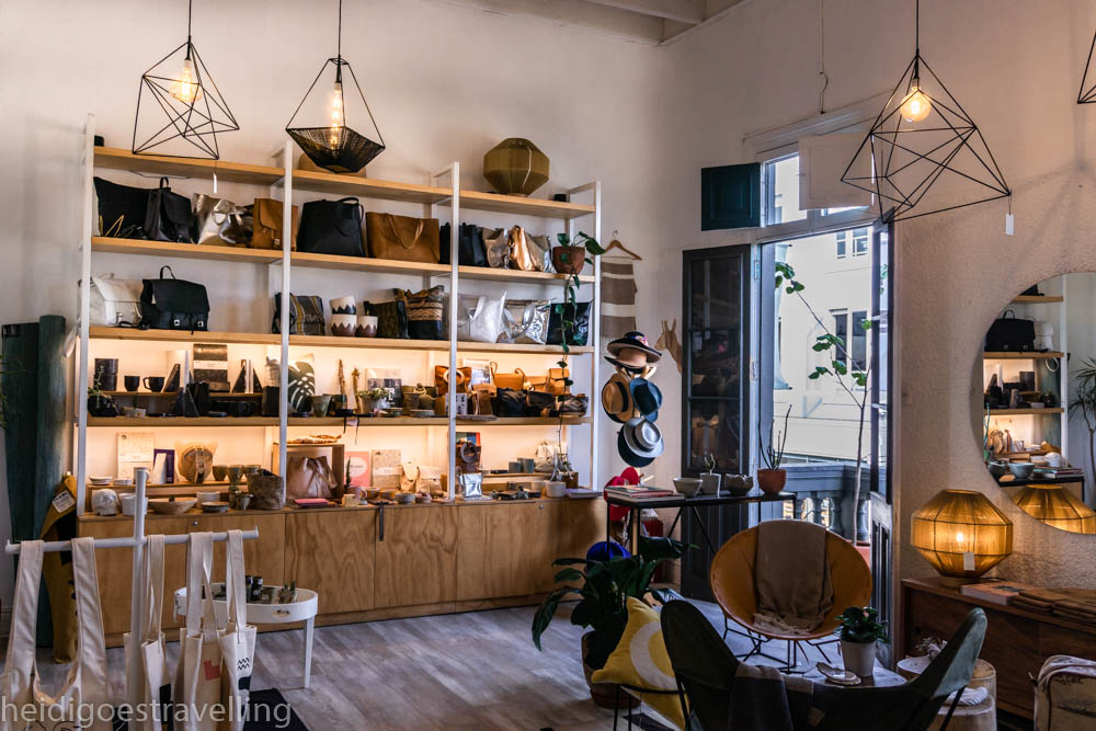 Picture of merchandise display inside a store, featuring huge wooden shelves showcasing fashion and decorative items, chairs and metal suspension lamps