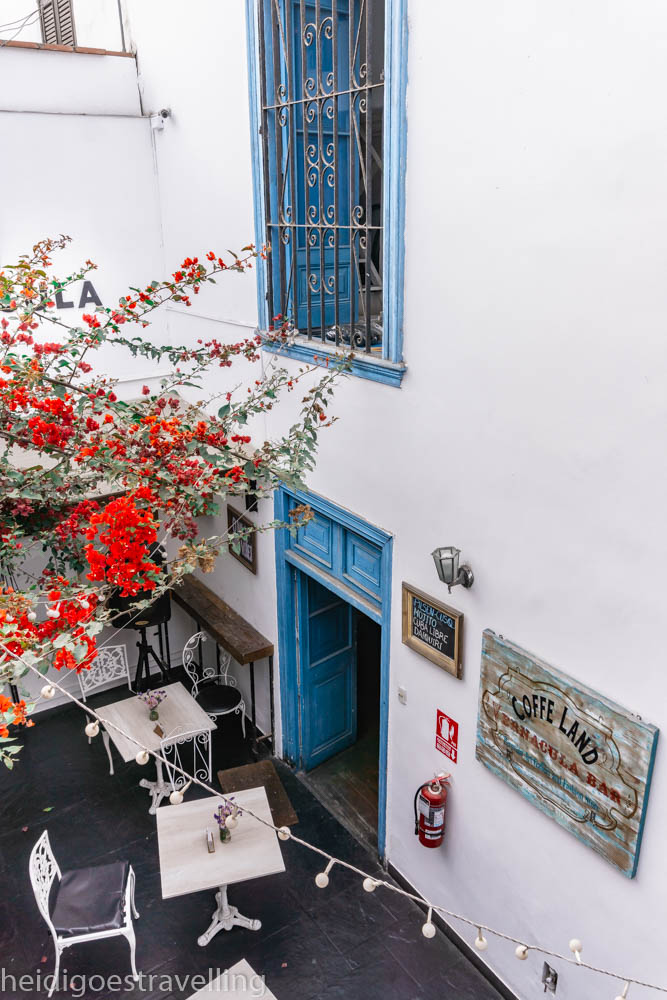 Picture of tiny intramuros patio with three marble and white metallic tables, a few white iron forged chairs, all overlooked by a red-ish bougainvillea