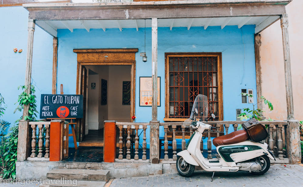 Picture view of baby-blue coloured small house with a wooden porch and white Vespa parked in front