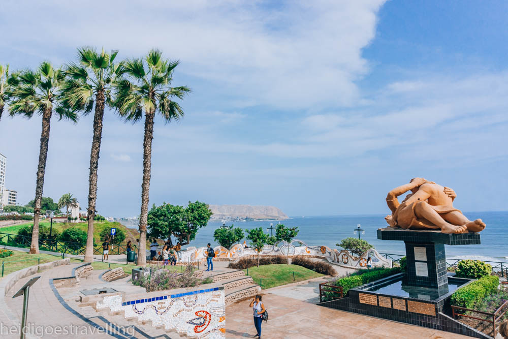 View of a small park by the ocean, with mosaic walls and a massive sculpture of two lovers kissing right in its center
