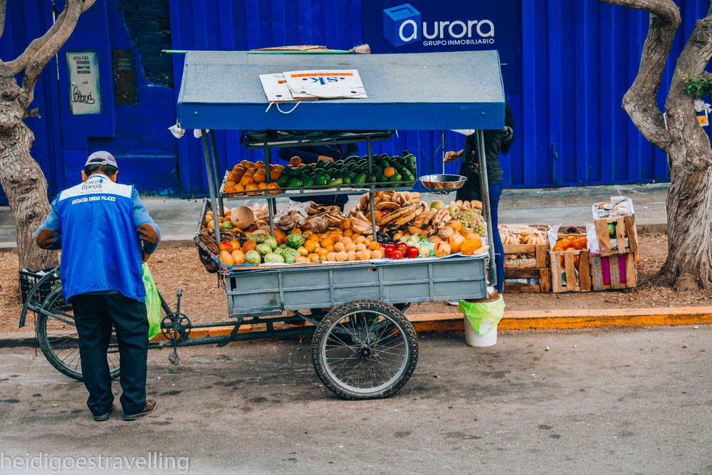 An old man selling fruits displayed on a cart