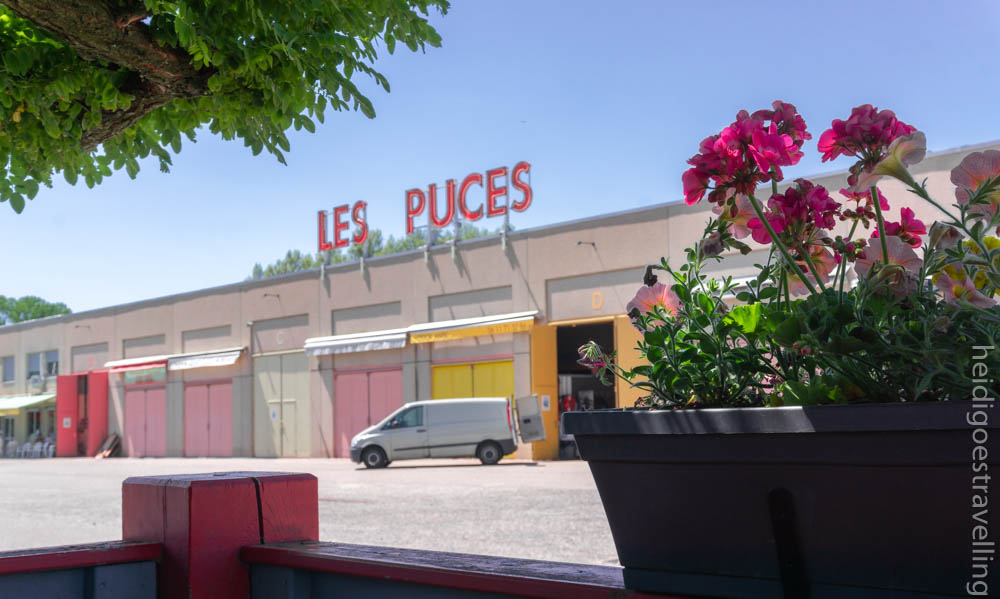 View of a building with 5 colourful hangar doors and on top of it giant letters reading Les Puces