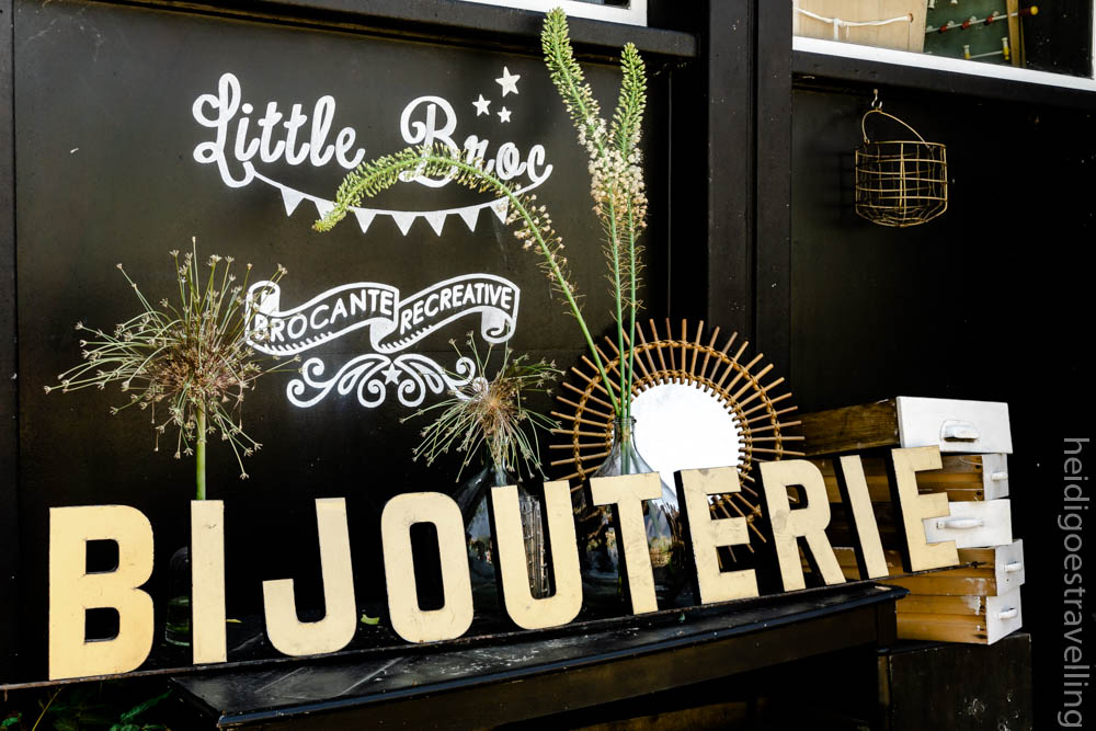 Picture of objects sold in a vintage furniture booth: big letters signs, a rattan mirror and wild flowers