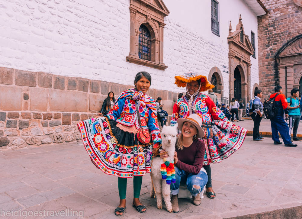Young women posing with two women dressed in their tradional very colourful costume and their baby alpaga