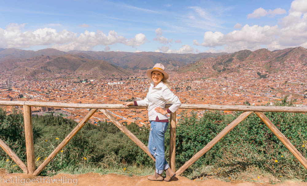 Young smiling woman leaning against a wooden barrier on a mountain overlooking the city of Cusco