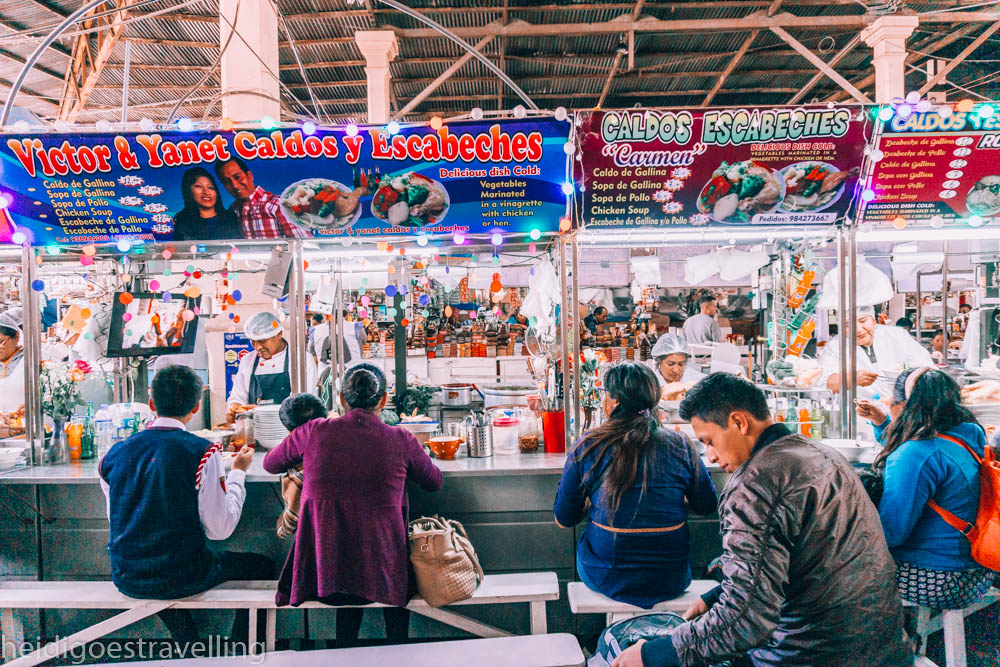 Bright coloured street food stall in San Pedro's indoor Market, Cusco with people eating