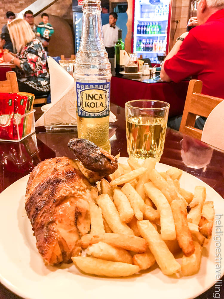 Close-up picture of grilled chicken wing, French fries and an Inca cola bottle