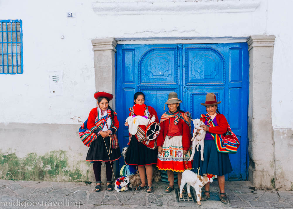Picture of 4 peruvian women dressed in their very colourful tradictionnal costume and holding two baby goats