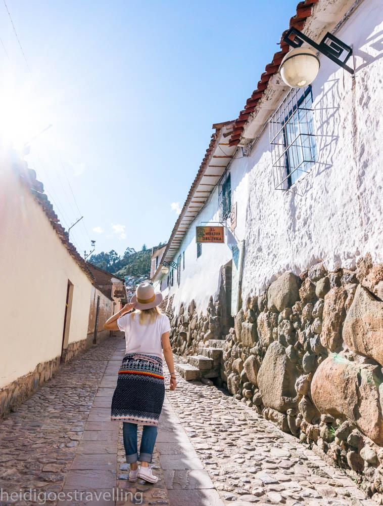 Young blond women walking up a cobblestone streets of San Blas, Cusco