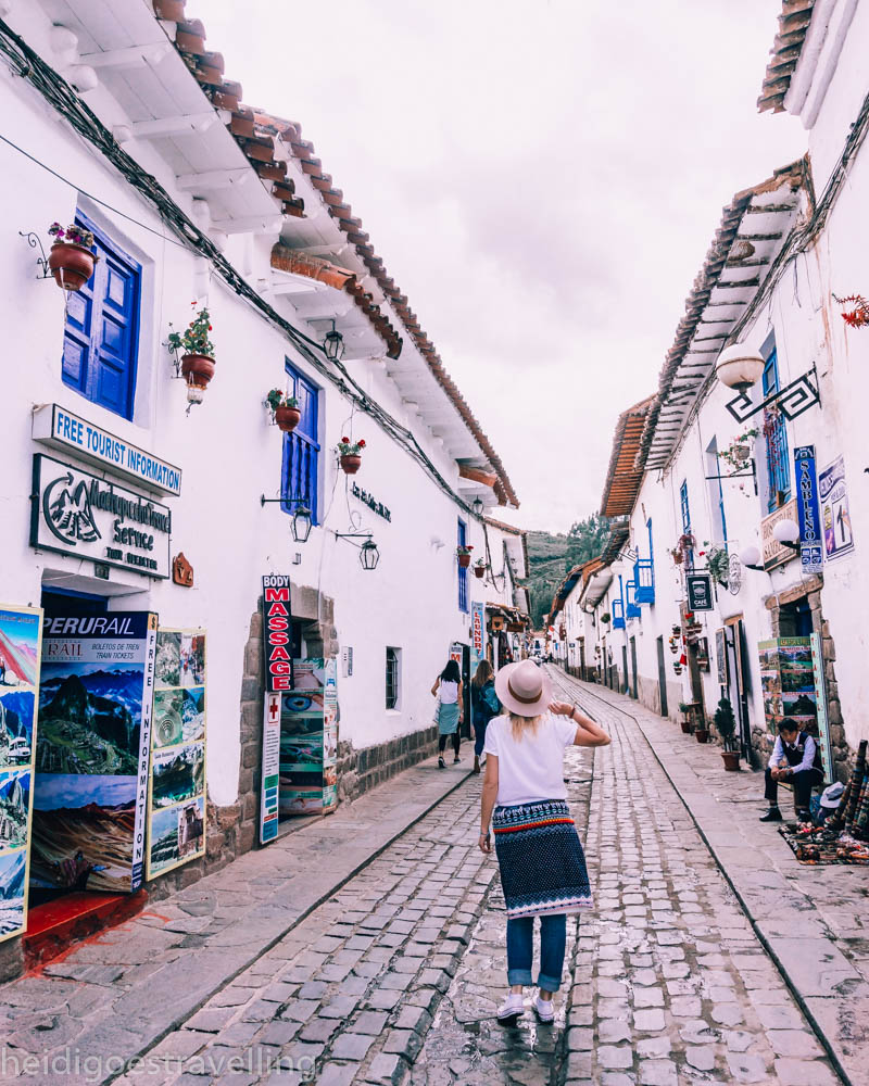 Young blond women walking up a cobblestone streets surrounded by white washed houses in San Blas, Cusco