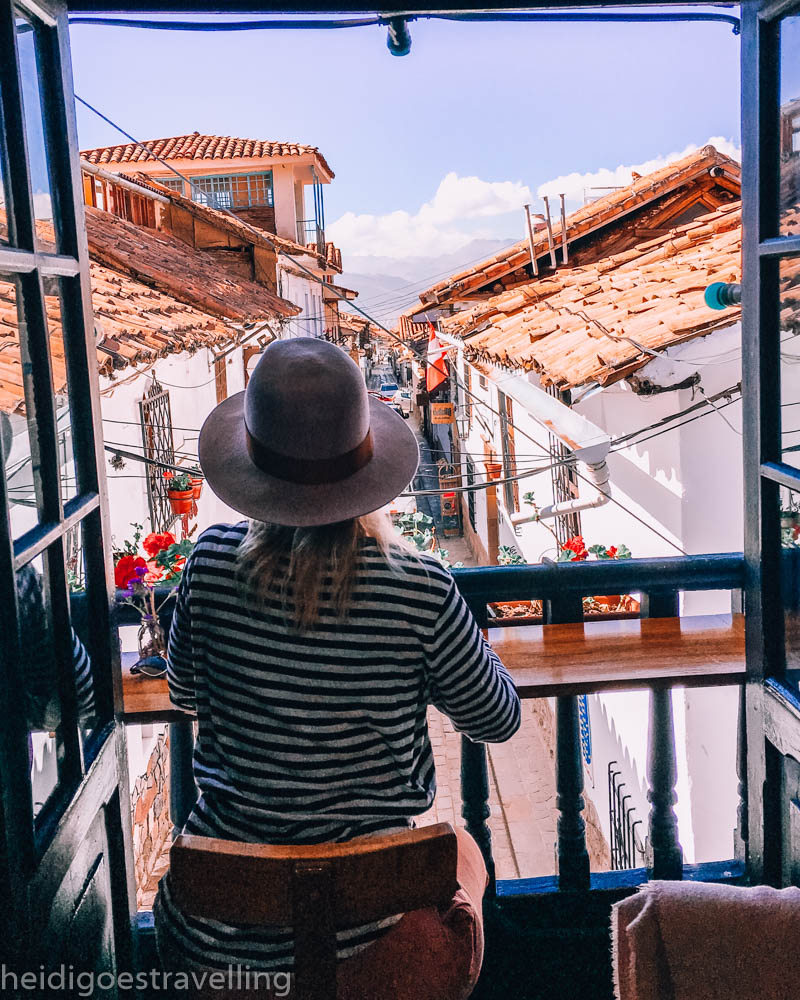 Young woman sitting on a tiny balcony overlooking a cobbledstone street in San Blas, Cusco