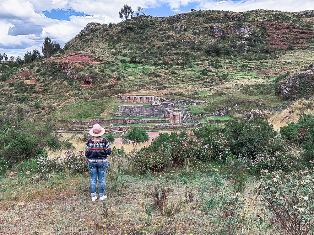 Young woman standing on a hill overlooking some ancient Inca ruins in Cusco