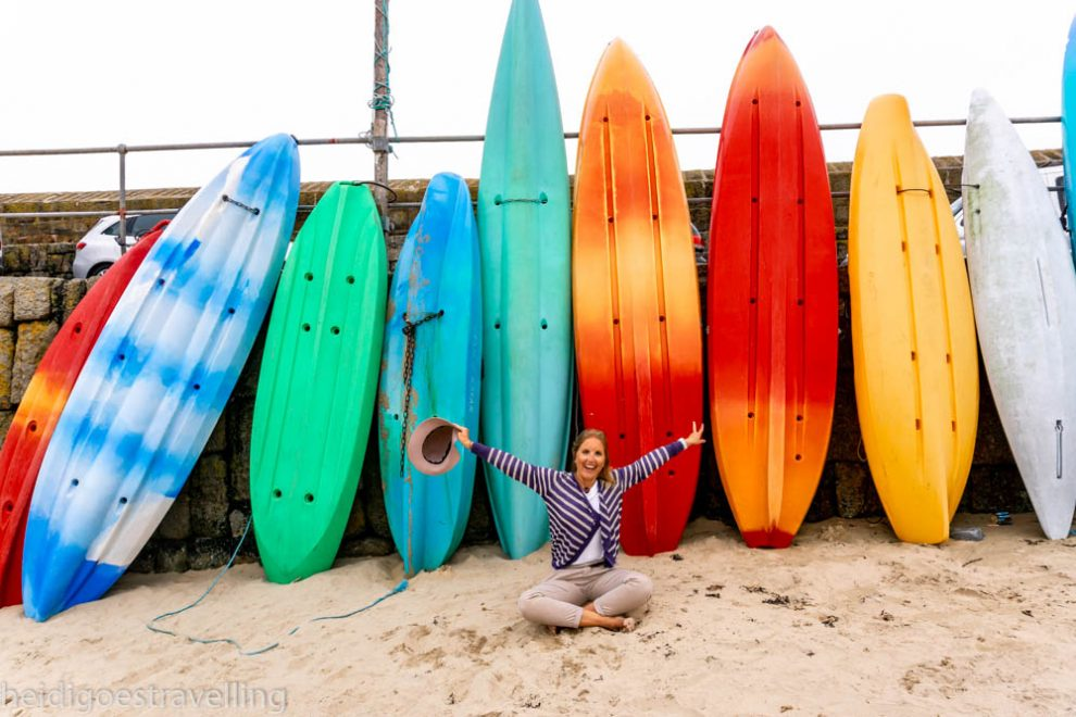 Young blond woman posing in front of several colourful surfboards stacked on a beach