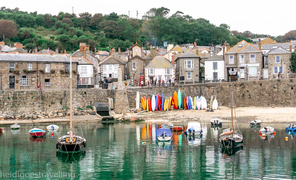 Landscape picture of greystone houses surrounding a small harbour and emerald green water