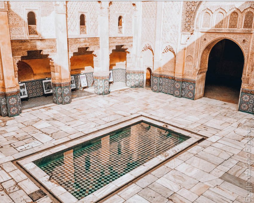 Internal courtyard of a traditional Moroccan building made of sand-coloured stone, mosaics and a waterbasin