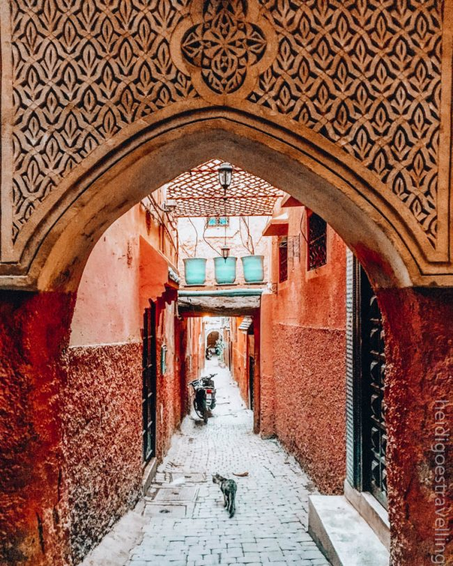 Sand and red-coloured arch facing a cobbled street