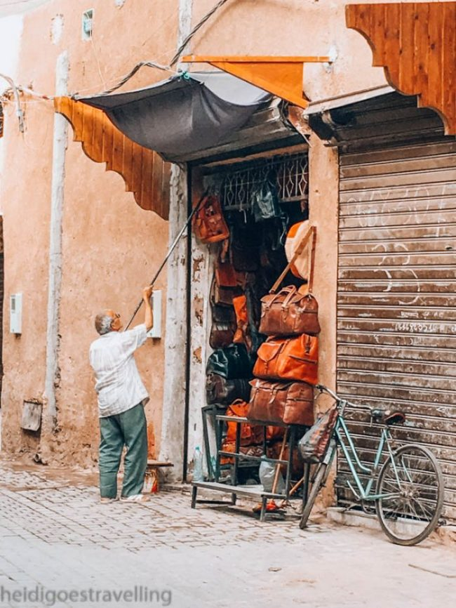 Old male shopkeeper installing the leather bags his sells directly on the street