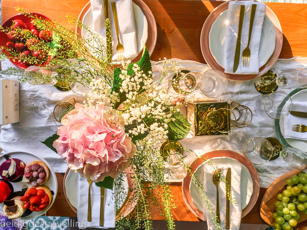 picnic table decorated with fresh flowers and pretty china