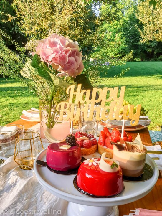 A fancy picnic table with on it 4 red and pink pastries with on top of them a birthday sign
