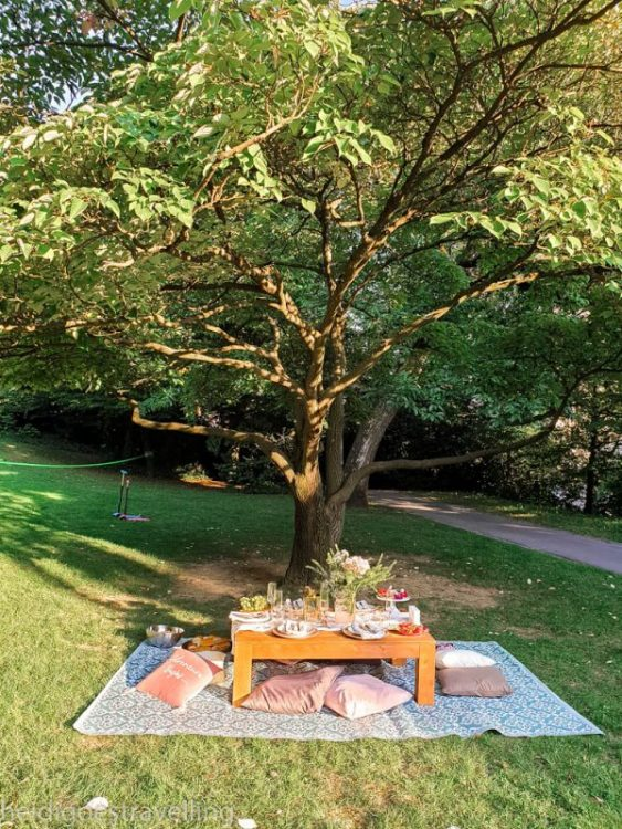 A large rectangular picnic table in a park and decorated with fresh flowers and pretty china