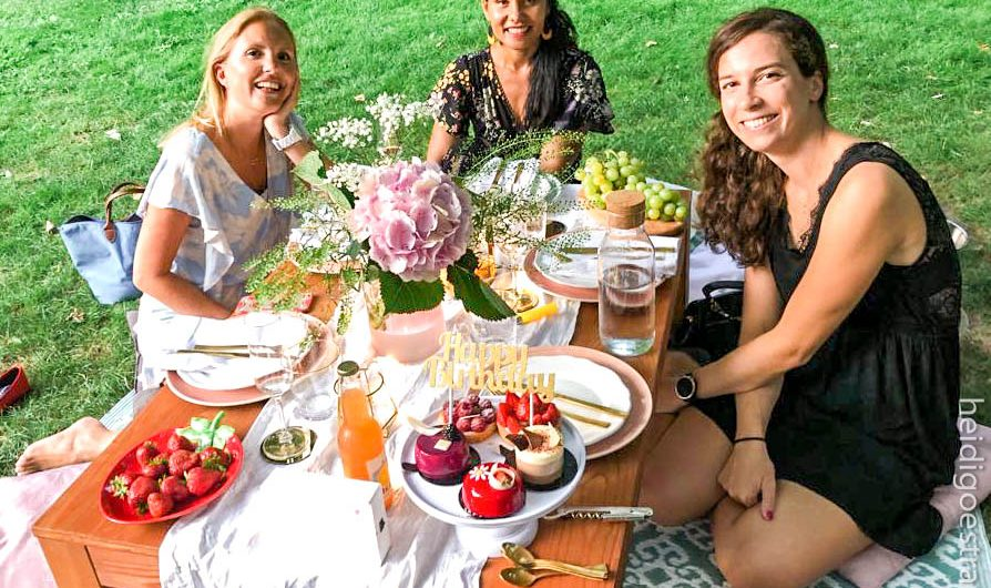3 young women around a large rectangular picnic table in a park and decorated with fresh flowers and pretty china