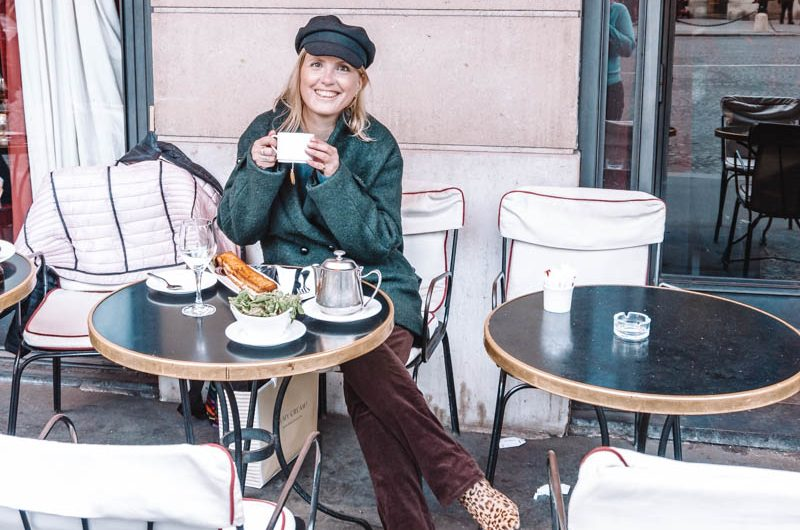 Young blonde woman wearing a black cap and green coat sitting on a iron chair on the terrace of a restaurant