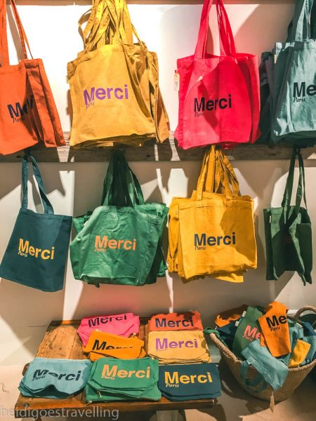 Colourful cotton bags and pencil cases with the word Merci glued on them