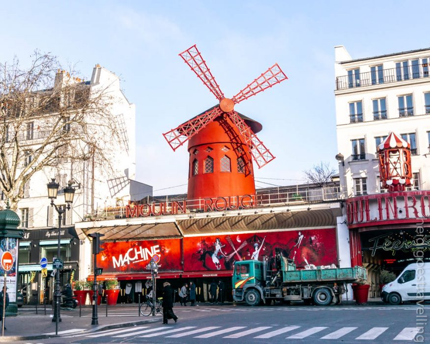Picture of a medium sized building with a red windmill on top of it and surrounded by two tall sized white-coloured buildings