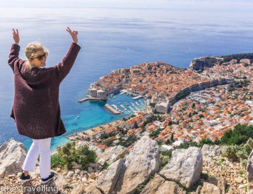 Young blonde woman standing on a cliff overlooking the city of Dubrovnik
