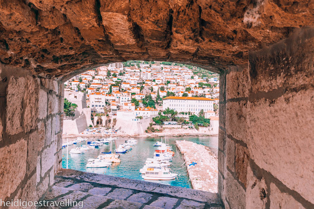 Tiny glassless window carved into a stone wall overlooking a harbour