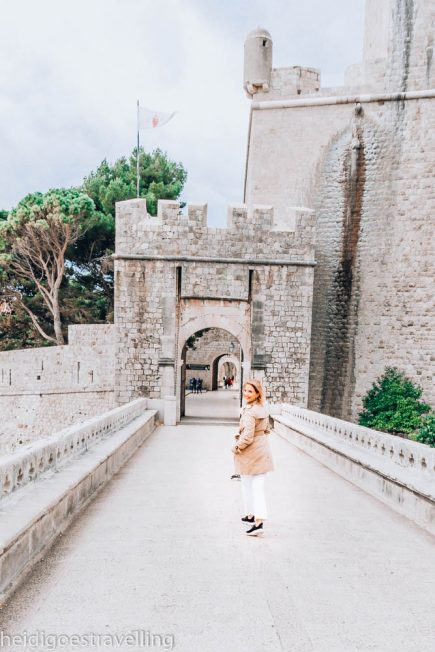Young blonde woman walking on a stone bridge facing an old stone gate
