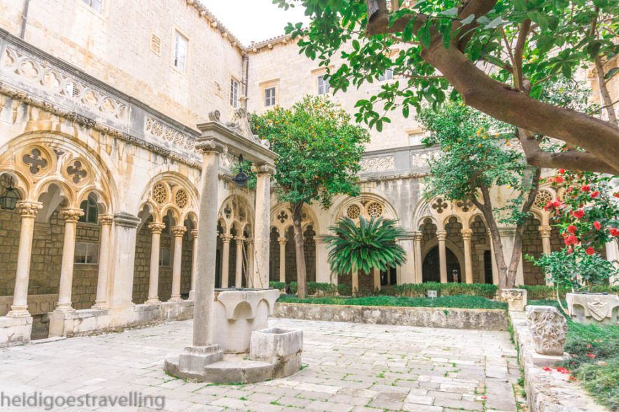 A square-shaped courtyard surrounded by gothic style arches and well in the middleth a wel