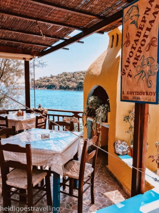 Picture of an outdoor taverna with 2 tables, several chairs and a big yellow fireplace
