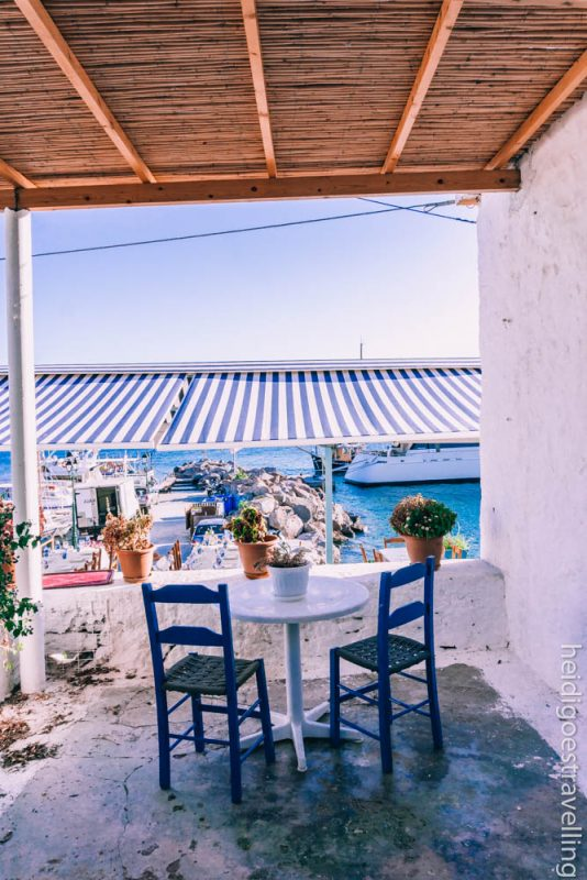 Picture of a small white table and two blue chairs on a white painted terrace facing a small harbour and the sea