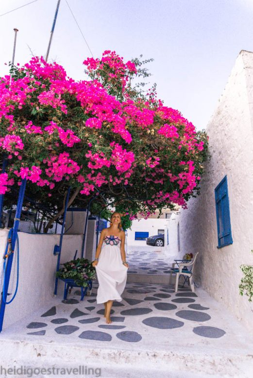Smiling young blond woman walking down a narrow white painted village street, with above her a hot pink bougainvillea