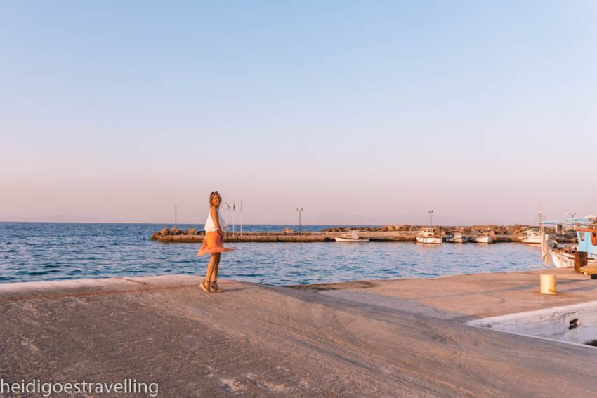 Young blond woman dancing on a pier in front of a blue sea and some fishing boats
