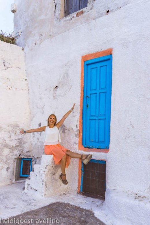 Smiling young blond woman sitting on white painted steps next to a sky blue door