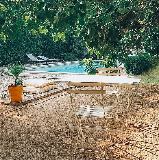 Picture of a table and two chairs on white/beige pebble stones and a pool in the background