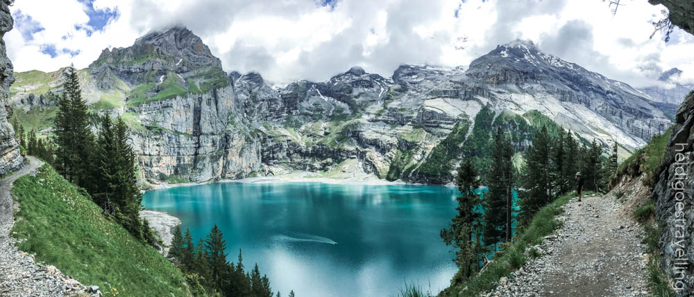 Picture of a deep turquoise blue lake surrounded by high mountains and lush green nature
