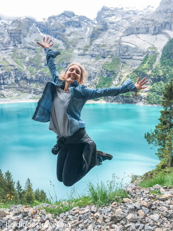 Young blond woman jumping on a cliff above a turquoise blue lake