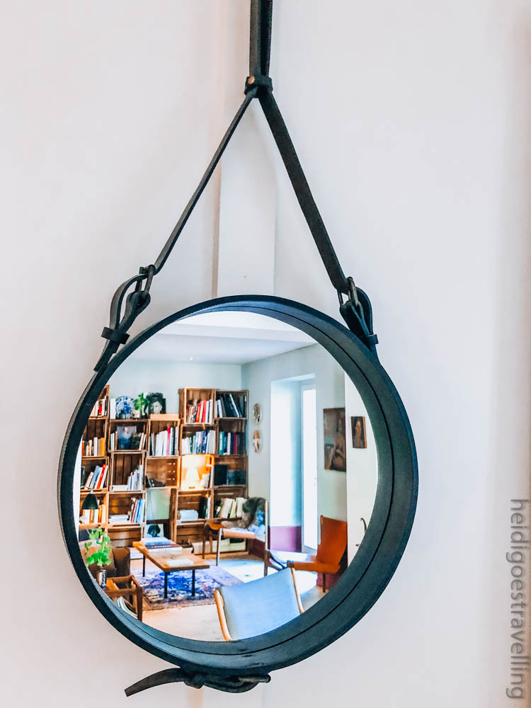 Picture of a round mirror hanging on a wall