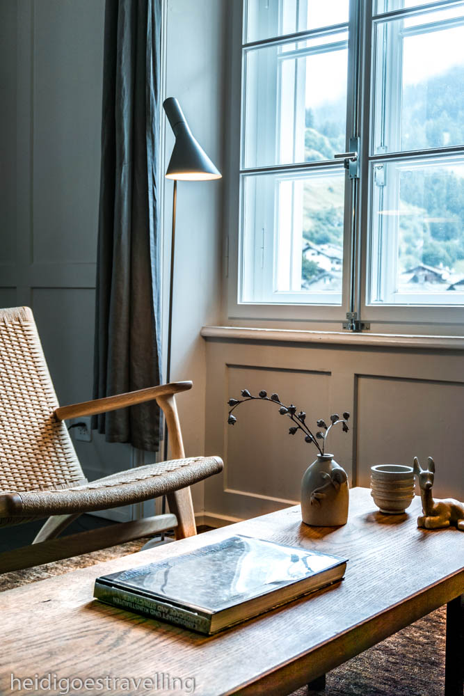 Picture of a wooden coffee table and a chair next to a big window