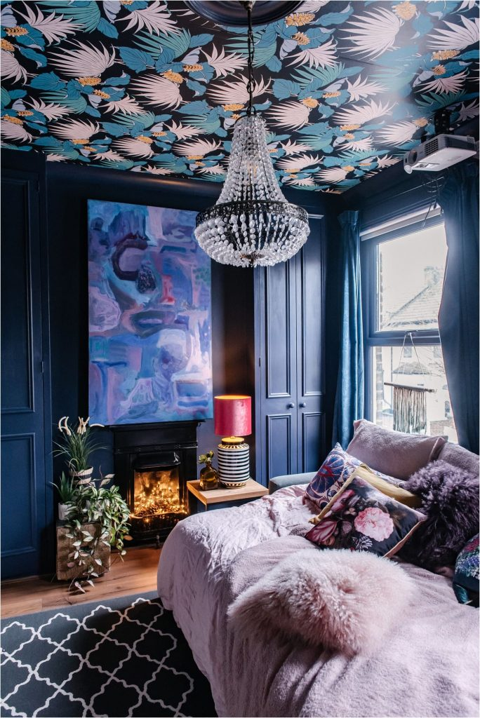 Picture of a sapphire blue room with a bold bird-patterned wallpaper on the ceiling