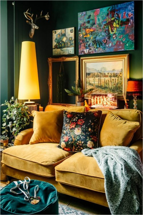 Picture of a mustard yellow velvet sofa placed below 4 paintings hanging on a dark green wall